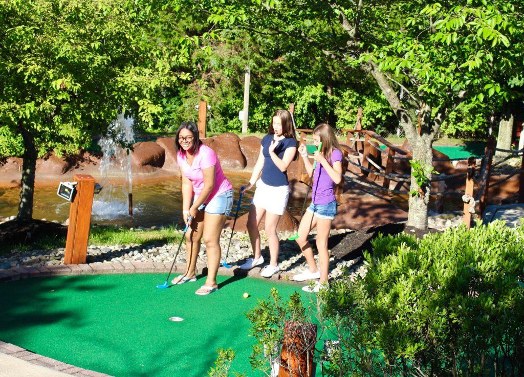 Three Girls Playing Miniature Golf Outside